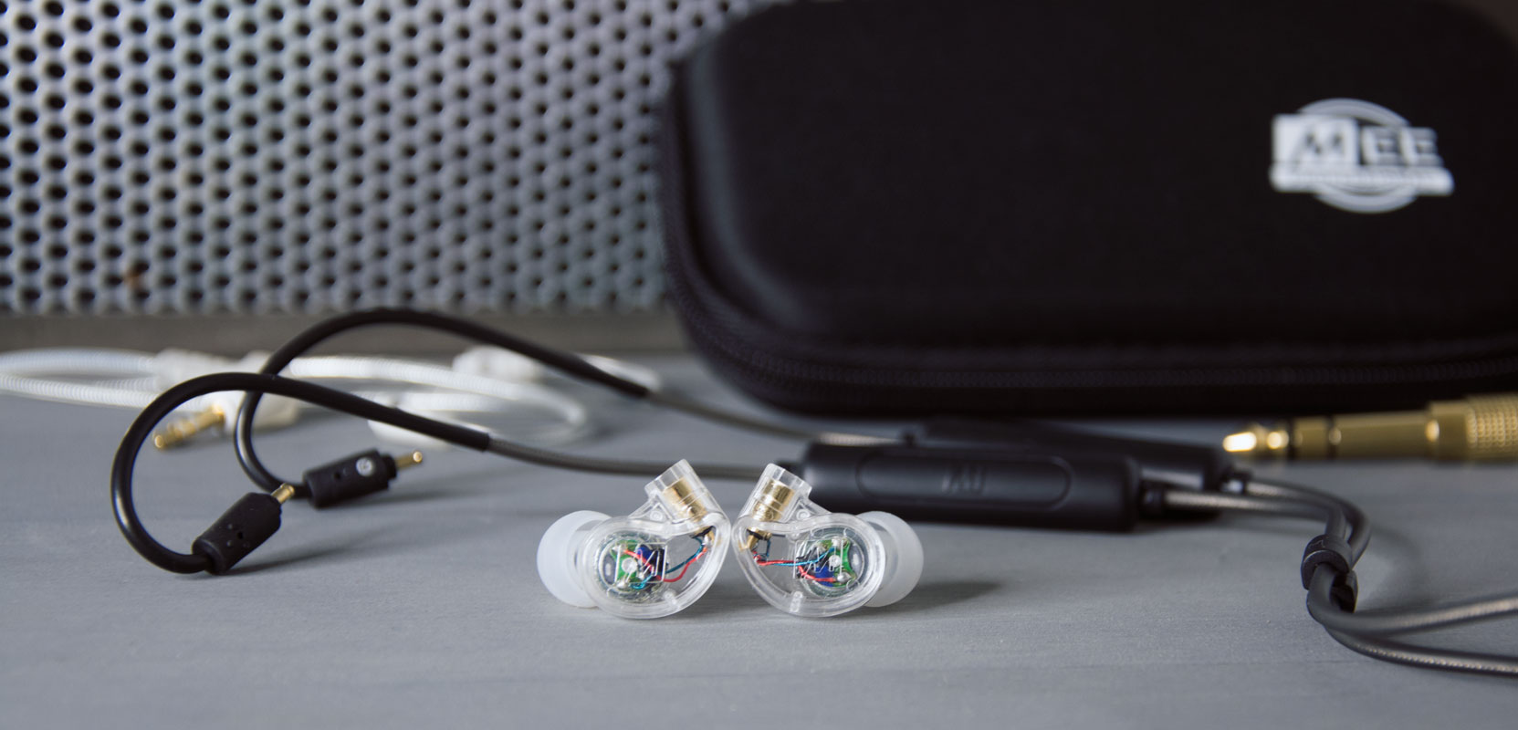 Pair of EP-M6PROG2 earpieces (clear) with detached Bluetooth adapter in background