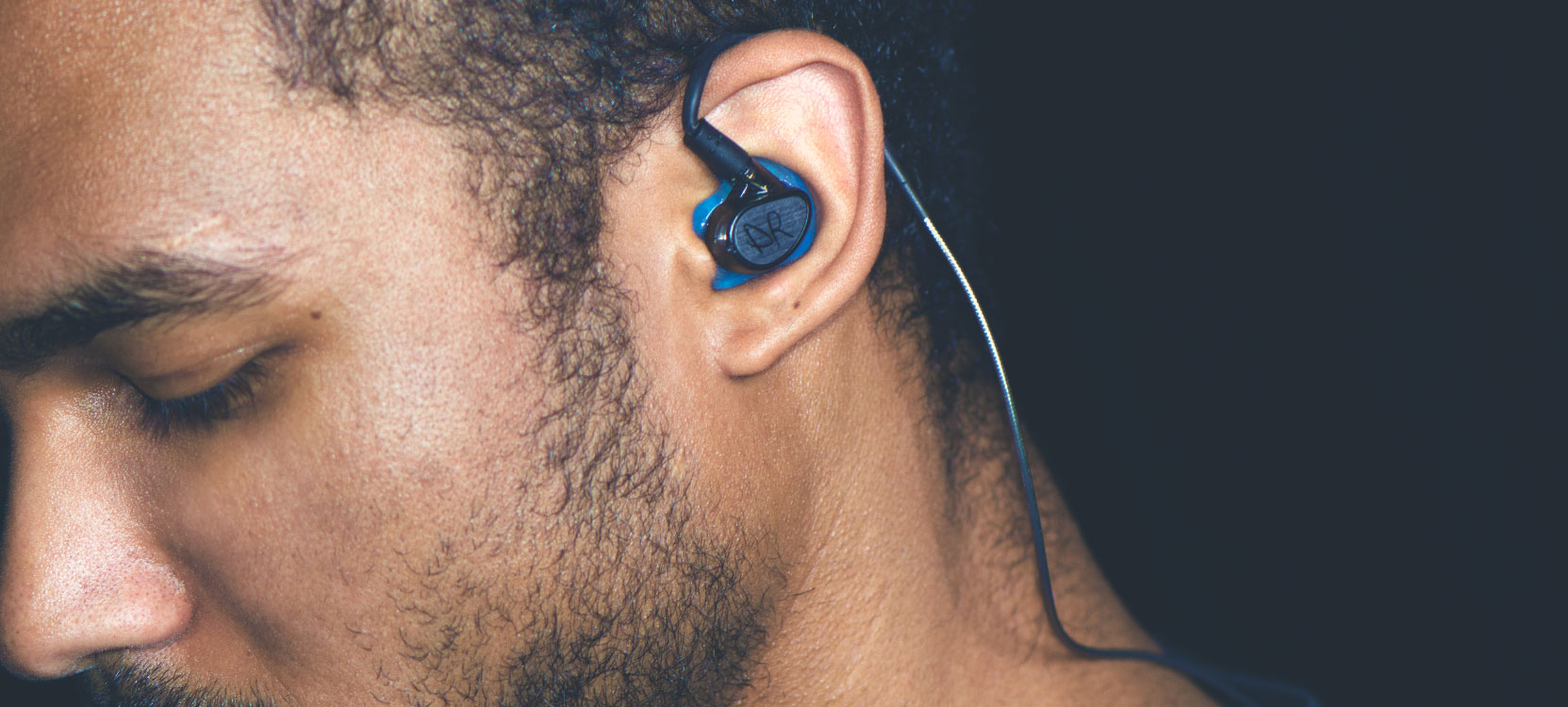 Man wearing MX PRO custom IEMs with blue eartips and engraved artwork