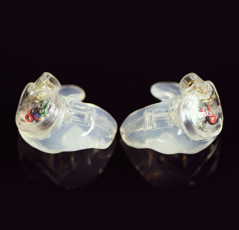 Pair of clear M6 PRO 1st generation earpiece with clear custom eartips on a shiny black background